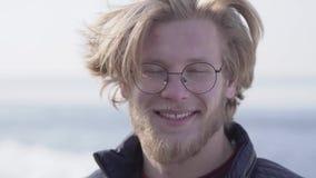 Портрет конца-вверх красивого бородатого человека в стеклах со светлыми волосами смотря в камере усмехаясь outdoors r сток-видео