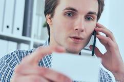 Портрет конца-вверх красивого европейского бизнесмена говоря на телефоне и держа визитную карточку на рабочем месте Стоковые Изображения