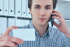 Портрет конца-вверх красивого европейского бизнесмена говоря на телефоне и держа визитную карточку на рабочем месте Стоковое Изображение