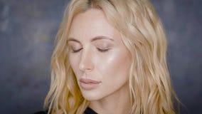 Портрет конца-вверх красивой белокурой модели с профессиональным макияжем, представляя против серой стены видеоматериал