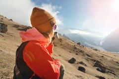 Портрет конца-вверх красивой девушки в шляпе и солнечных очках с кружкой кофе или чая пока сидящ на камне внутри стоковая фотография
