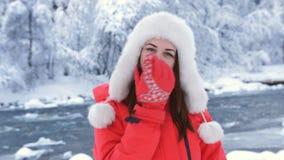 Портрет конца-вверх красивой женщины в красной куртке и крышка в древесинах около роют реки видеоматериал