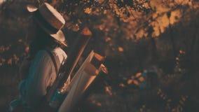 Портрет конца-вверх красивой маленькой девочки с длинной соломенной шляпой темных волос нося Она играет с ее волосами в теплом акции видеоматериалы