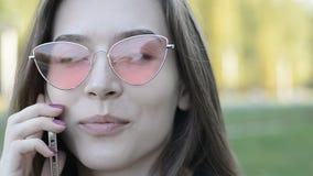 Портрет конца-вверх красивой молодой женщины в розовых солнечных очках которая говорит на телефоне в парке видеоматериал