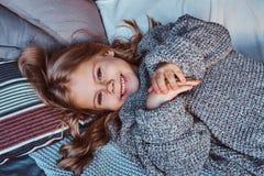 Портрет конца-вверх маленькой девочки в теплом свитере лежа на кровати стоковые изображения