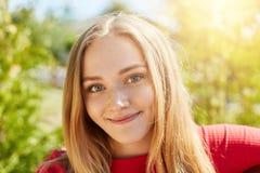 Портрет конца-вверх милой женщины с справедливыми прямыми волосами, очаровательными зелеными глазами и gentle улыбка нося красные Стоковая Фотография
