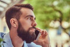 Портрет конца-вверх модного бородатого мужчины с стильной стрижкой, говорящ телефоном, сидя в кафе outdoors стоковое изображение rf