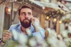 Портрет конца-вверх модного бородатого мужчины с стильной стрижкой, говорящ телефоном, сидя в кафе outdoors стоковая фотография rf