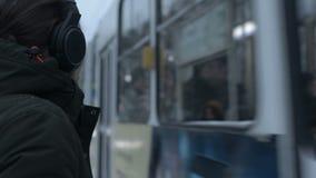 Портрет конца-вверх молодого длинн-с волосами человека с бородой в наушниках стоя на трамвайной остановке в зиме и ожидании сток-видео