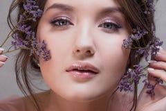 Портрет конца-вверх молодого привлекательного и красивого брюнета Свежий взгляд весны с цветками стоковое изображение