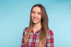 Портрет конца-вверх молодой кавказской усмехаясь женщины на голубой предпосылке стоковые фотографии rf