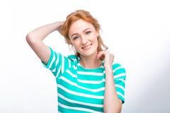 Портрет конца-вверх молодой, красивой женщины с красным вьющиеся волосы в платье лета с прокладками сини в студии на сером ба стоковое изображение rf