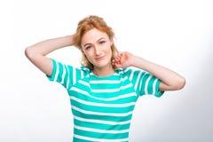 Портрет конца-вверх молодой, красивой женщины с красным вьющиеся волосы в платье лета с прокладками сини в студии на сером ба стоковые фото