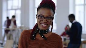 Портрет конца-вверх молодой красивой черной бизнес-леди специалисту по дизайна в умных eyeglasses усмехаясь на светлом офисе акции видеоматериалы