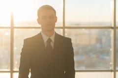 Портрет конца-вверх молодого красивого бизнесмена, смотрящ серьезно на камере, стоя в светлом офисе над большим стоковое фото rf