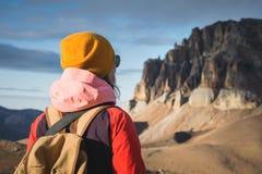 Портрет конца-вверх от задней части путешественника девушки в куртке с крышкой и рюкзаком стоит на предпосылке  стоковое изображение rf
