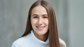 Портрет конца-вверх очаровывать представлять молодой европейской женщины усмехаясь в студии на серой предпосылке сток-видео