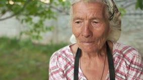 Портрет конца-вверх очень старухи в ее саде Больш-бабушка говорит что-то к себе, читает молитву сток-видео