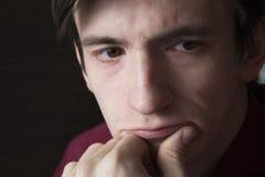 Портрет конца-вверх парня, кулака подпирая его щеку Стоковые Изображения