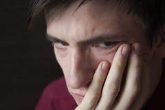 Портрет конца-вверх парня, унылого тяжелого взгляда, кулака подпирая его щеку Стоковая Фотография