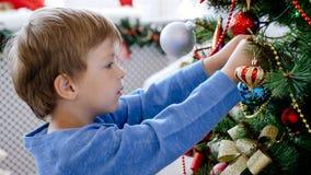 Портрет конца-вверх ребенка украшая рождественскую елку, крупный план стоковое фото rf