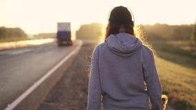 Портрет конца-вверх рыжеволосой девушки в наушниках идя вдоль обочины на заходе солнца задний взгляд движение медленное акции видеоматериалы