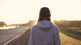 Портрет конца-вверх рыжеволосой девушки в наушниках идя вдоль обочины на заходе солнца задний взгляд движение медленное сток-видео