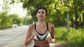 Портрет конца-вверх спортсмена Девушка бежать вдоль дороги на заходе солнца Молодая женщина делая спорт в природе медленно сток-видео