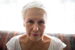 Портрет конца-вверх старшей женщины сидя на софе против окна Стоковые Изображения RF