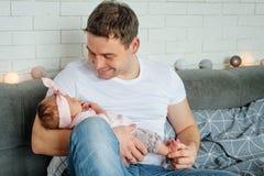 Портрет конца-вверх счастливого молодого отца обнимая и целуя его сладостный прелестный новорожденный ребенка семья принципиально стоковые изображения