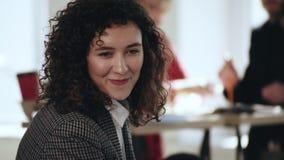 Портрет конца-вверх счастливой красивой молодой кавказской бизнес-леди предпринимателя усмехаясь, говоря на современном офисе сток-видео