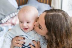 Портрет конца-вверх счастливой молодой матери обнимая и целуя его сладостного прелестного ребенка Внутри помещения снял, изображе Стоковые Изображения RF