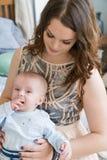 Портрет конца-вверх счастливой молодой матери обнимая и целуя его сладостного прелестного ребенка Внутри помещения снял, изображе Стоковое Фото