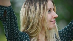 Портрет конца-вверх счастливой привлекательной кавказской белокурой девушки с влажными волосами во время дождя на природе на откр видеоматериал