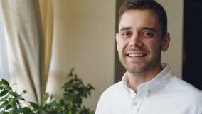 Портрет конца-вверх темн-с волосами красивого молодого человека в белой рубашке усмехаясь и смотря камеру человек предпосылки сча сток-видео