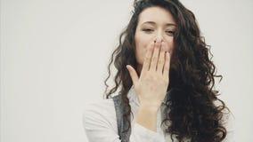 Портрет конца-вверх удивленной молодой красивой бизнес-леди брюнета Игра волос во время этого отправляет поцелуй с воздухом акции видеоматериалы