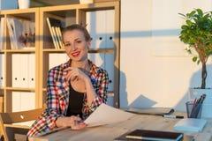 Портрет конца-вверх усмехаясь бумаги чтения женщины на ее рабочем месте, смотря камеру на солнечный день в светлой комнате офиса Стоковое Фото