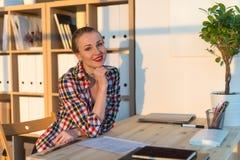 Портрет конца-вверх усмехаясь бумаги чтения женщины на ее рабочем месте, смотря камеру на солнечный день в светлой комнате офиса Стоковая Фотография