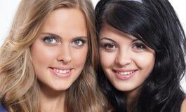 Портрет конца-вверх 2 усмехаясь молодых женских друзей против wh Стоковая Фотография