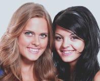 Портрет конца-вверх 2 усмехаясь молодых женских друзей против wh стоковое изображение