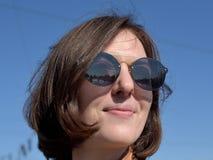 Портрет конца-вверх усмехаясь туриста молодой дамы в солнечных очках Санкт-Петербурга России нося стоковая фотография