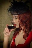 Портрет конца-вверх элегантной молодой женщины redhead в красном платье, имеющ стекло красного вина Стоковые Фото