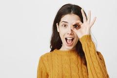 Портрет конца-вверх excited счастливого кавказского о'кей показа студентки или штраф подписывают сверх глаз, стоя с открытым ртом стоковые изображения