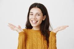 Портрет конца-вверх excited счастливой симпатичной женщины усмехаясь жизнерадостно пока распространяющ вручает около плеч и стоковые фото