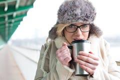 Портрет кофе женщины выпивая от изолированного контейнера питья во время зимы Стоковое Изображение