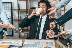 портрет кофе и сидеть занятого бизнесмена выпивая на рабочем месте пока коллеги помогая с работой Стоковое Изображение RF