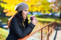 Портрет кофе молодой красивой женщины выпивая в парке осени Стоковая Фотография RF