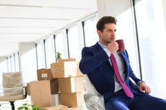 Портрет кофе молодого бизнесмена выпивая с moving коробками в предпосылке на офисе Стоковые Изображения