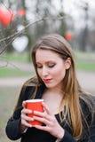 Портрет кофе молодой красивой стильной девушки выпивая в парке Стоковое фото RF