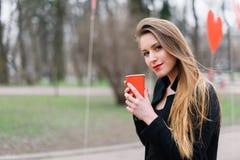 Портрет кофе молодой красивой стильной девушки выпивая в парке Стоковое Фото